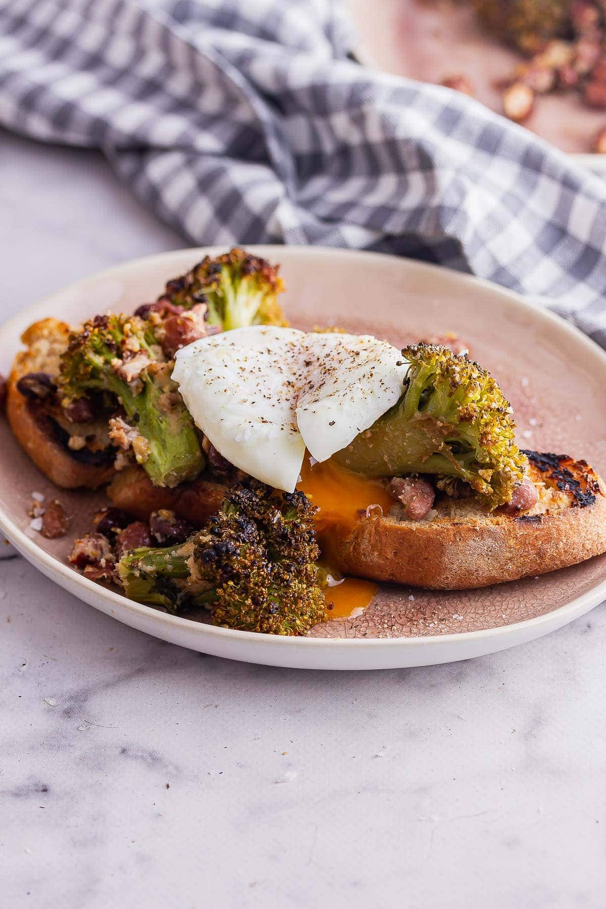 Pink plate of miso broccoli with a runny poached egg on a marble surface