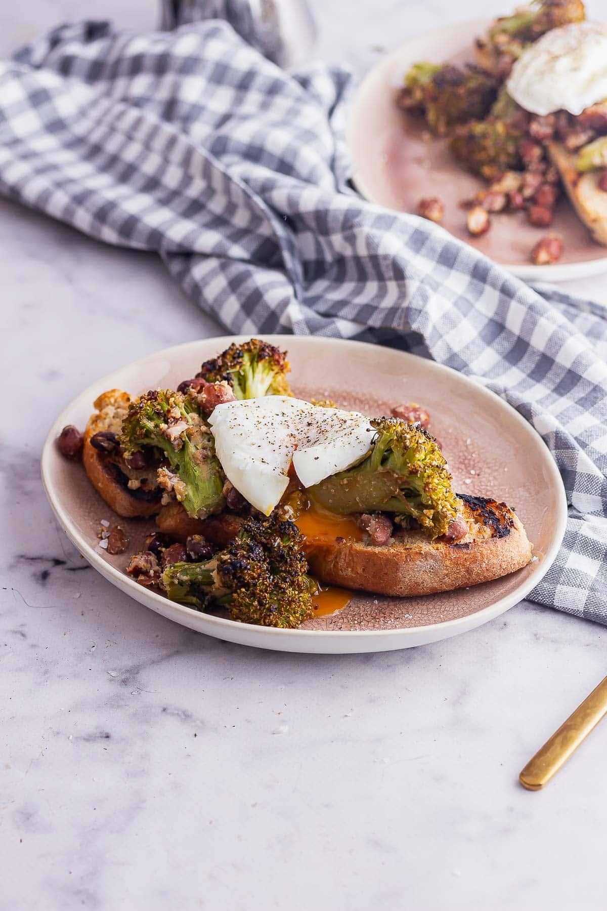 Runny poached egg on broccoli and bean toasts on a marble surface