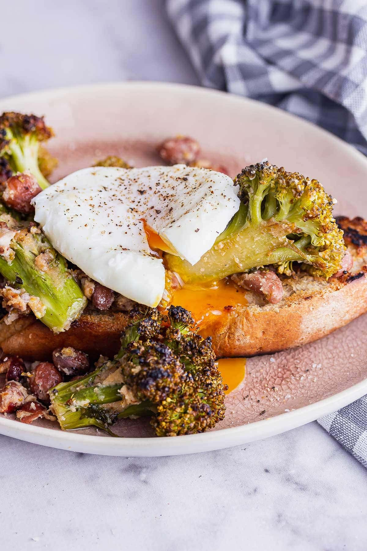 Close up shot of runny egg on broccoli toast