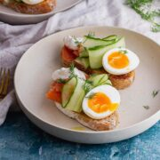 White bowl of smoked salmon toasts with egg and cucumber