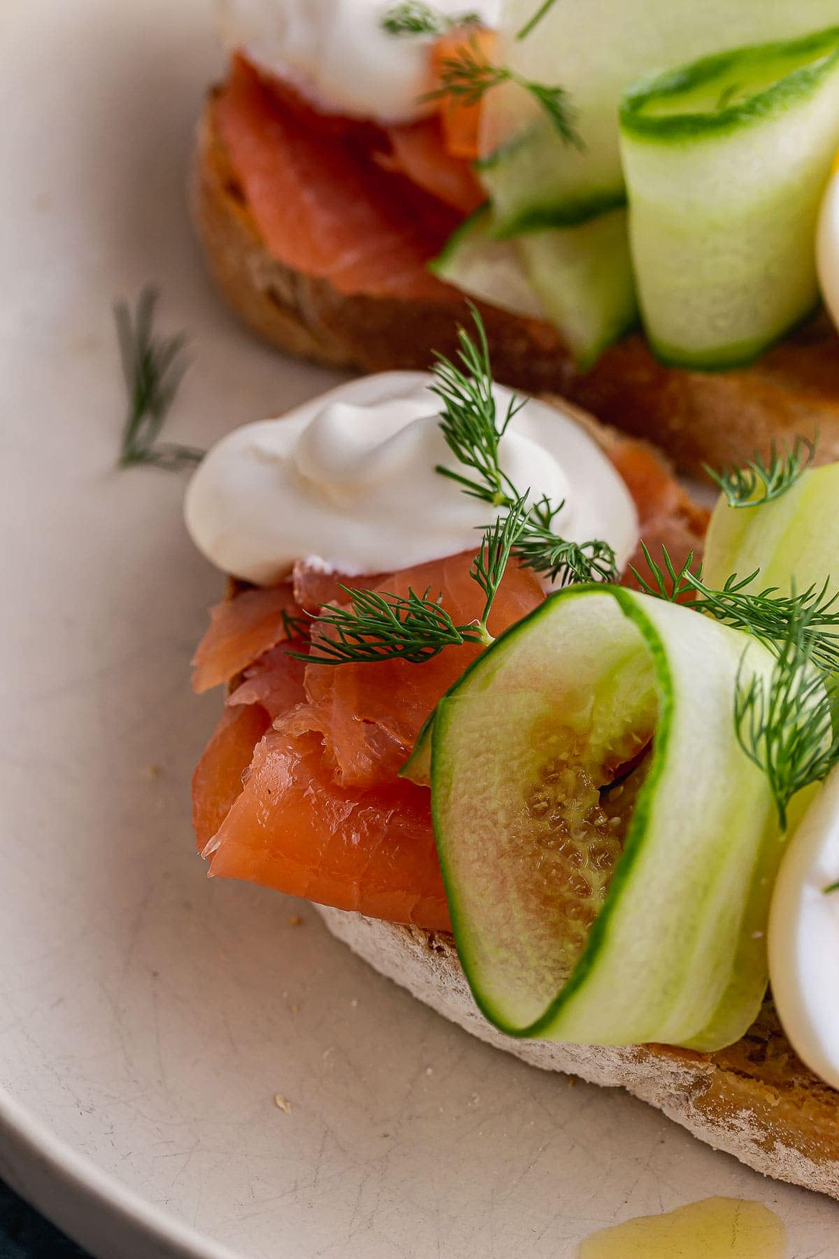Close up of smoked salmon, cucumber and creme fraiche on toast