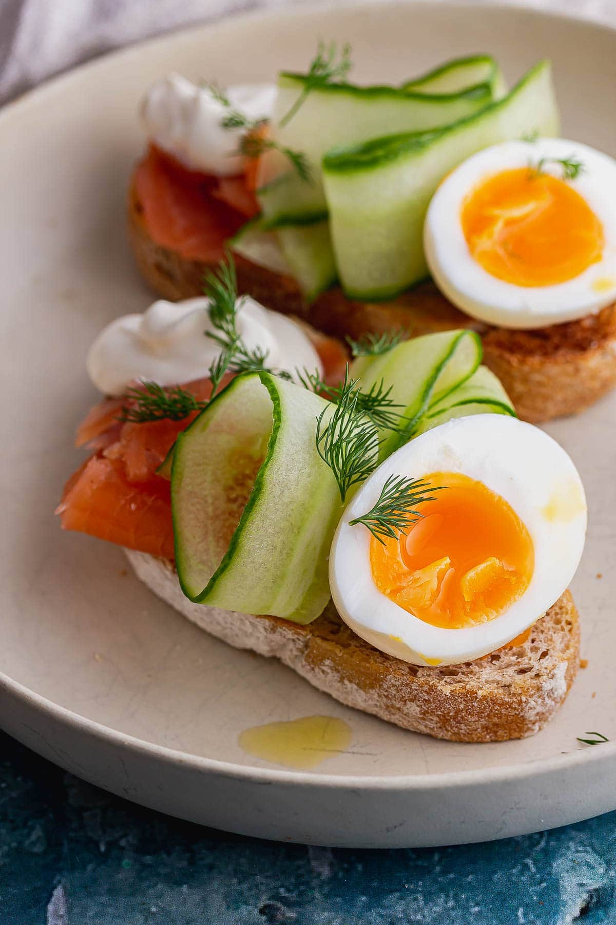 Close up of runny eggs on toast with salmon and cucumber