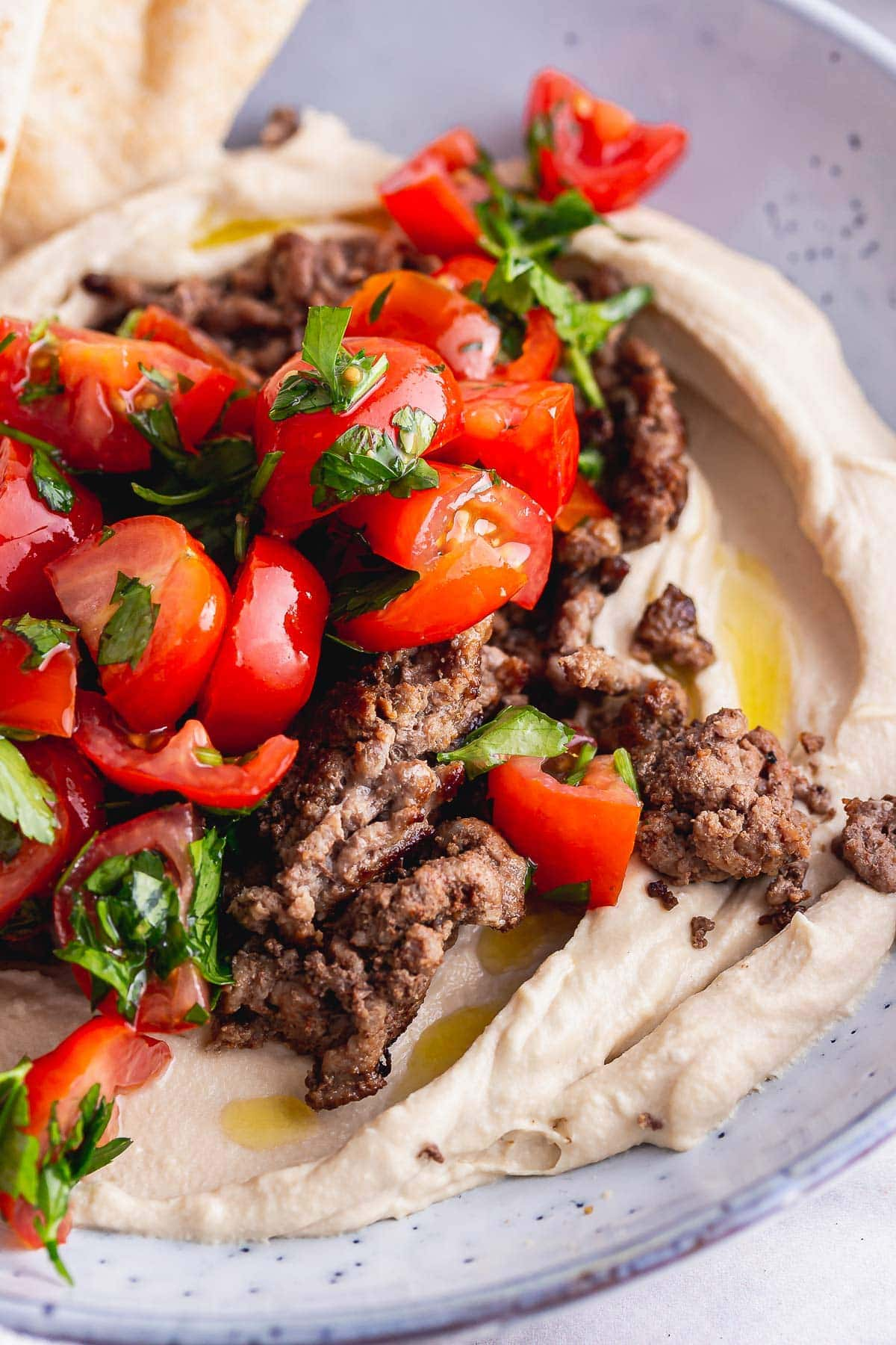 Close up of spiced beef hummus bowls with tomato