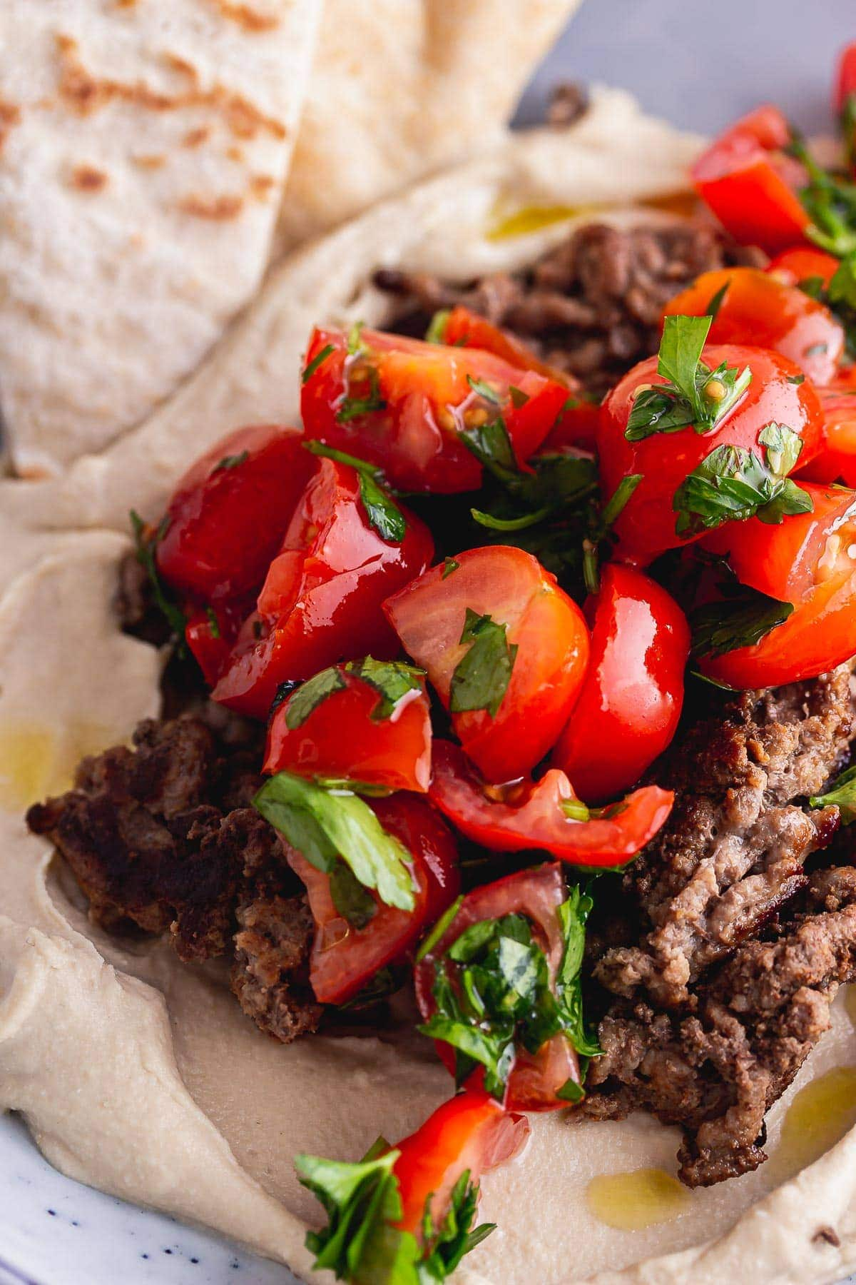 Close up of tomatoes on beef and hummus