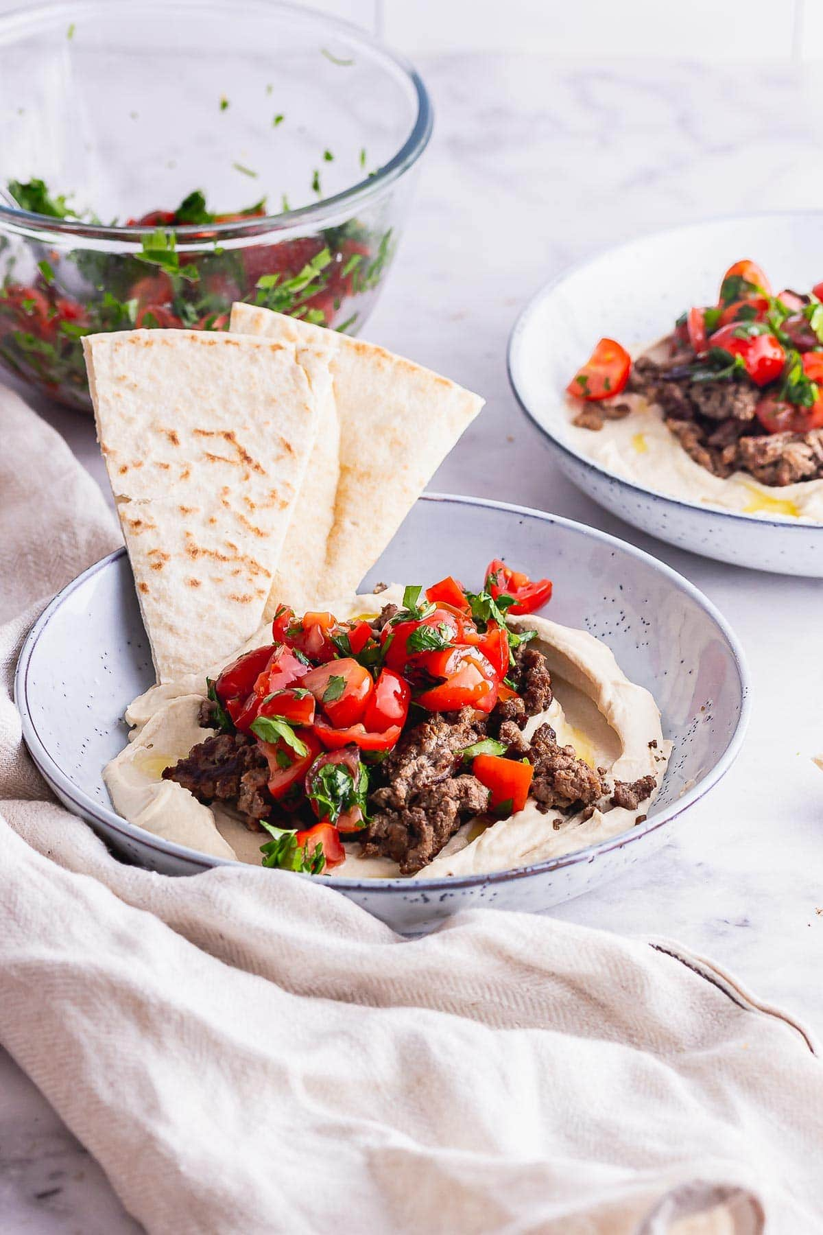 Side shot of beef bowls with hummus with pitta