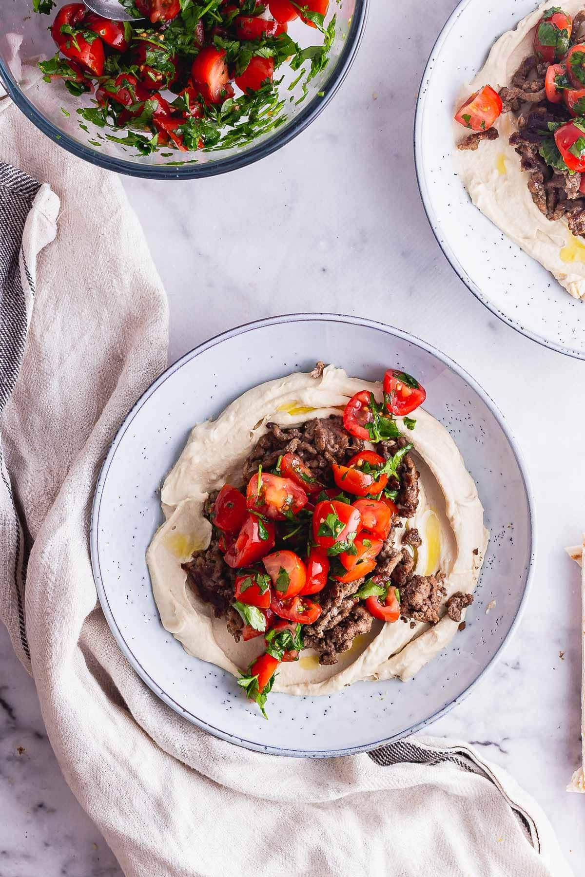 Overhead shot of beef and hummus bowl with bowl of tomatoes