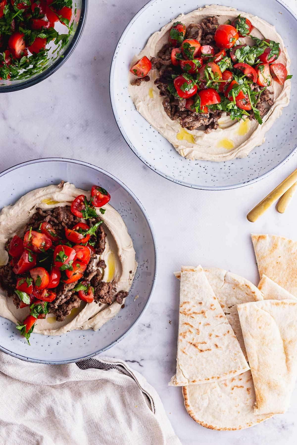 Overhead shot of two bowls of hummus on a marble background with pitta