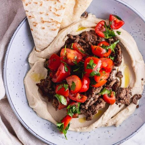 Overhead shot of blue bowl of spiced beef and hummus with pitta