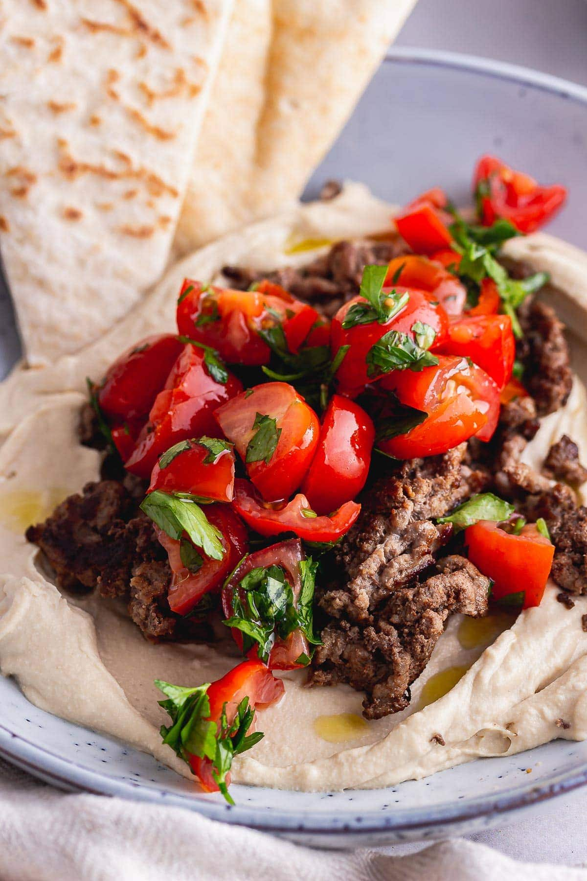Close up of tomatoes and beef on hummus