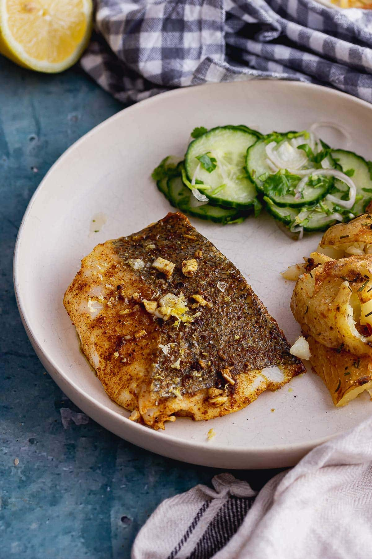 Spiced fish on a white plate with cucumber salad