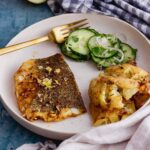 Fish, potatoes and cucumber in a white bowl with a checked cloth