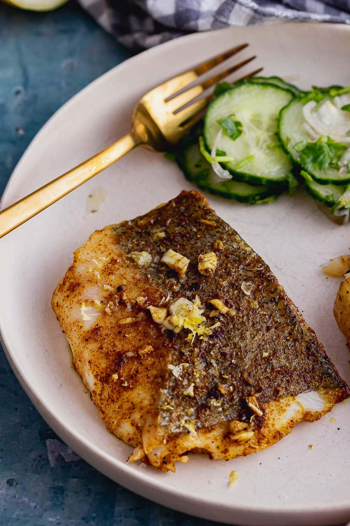 Baked fish fillet in a white bowl with cucumber