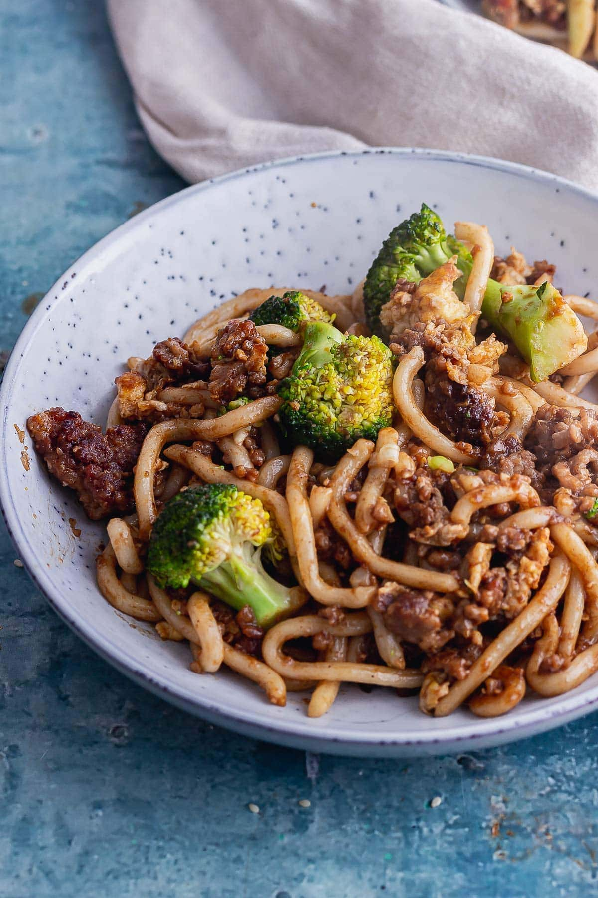 Bowl of udon noodle stir fry with pork and broccoli