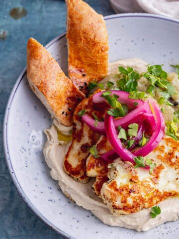 Close up of hummus and halloumi with bread in a blue bowl