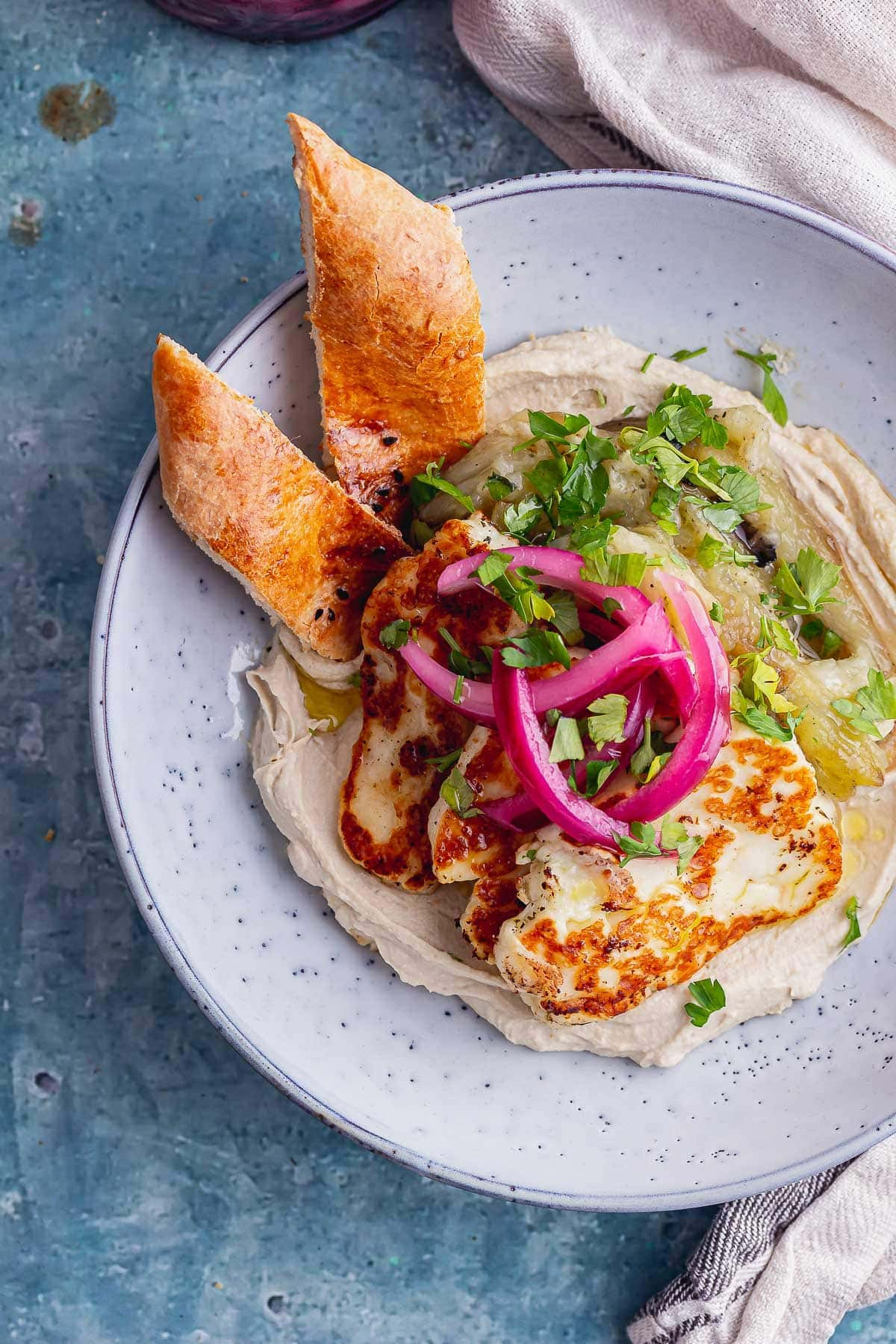 Overhead shot of halloumi aubergine hummus bowl with bread in a blue bowl