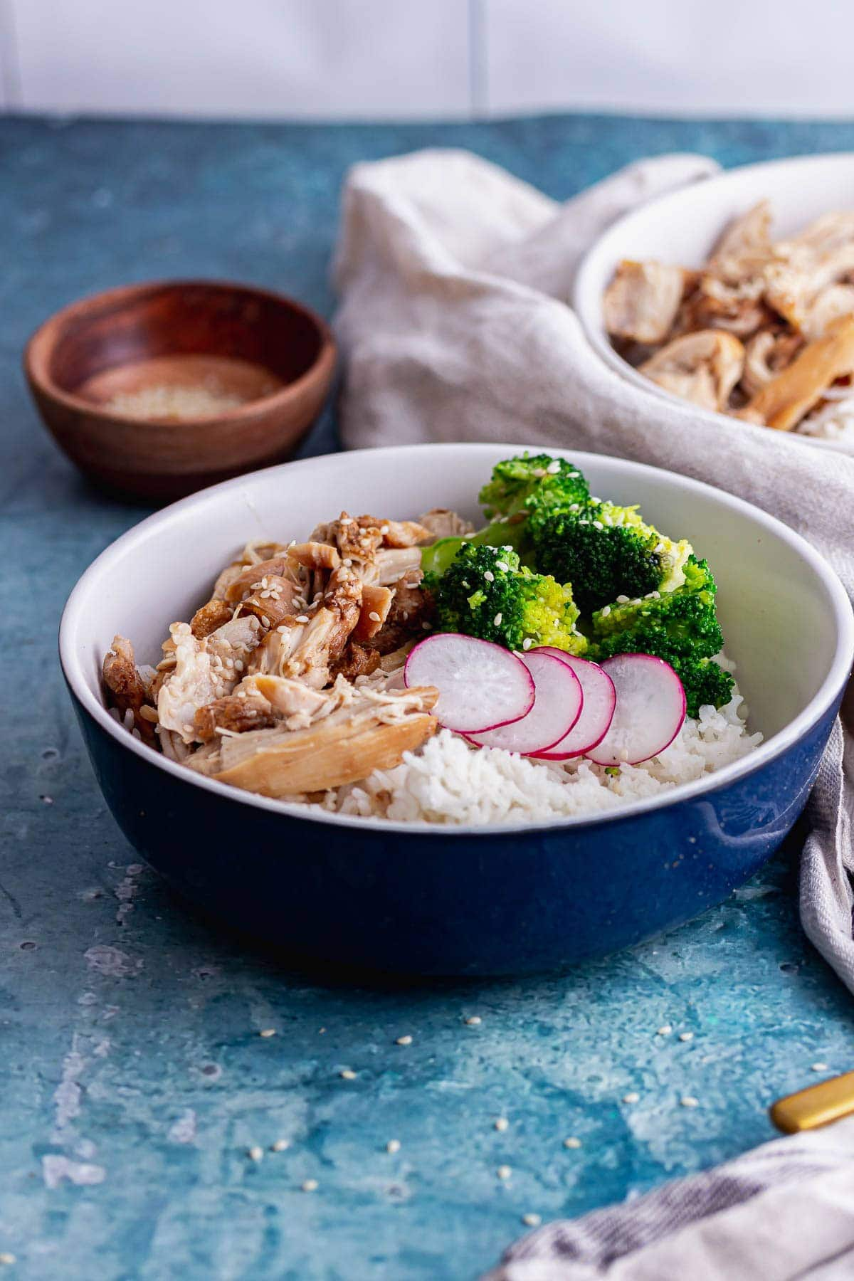 Blue bowl of pressure cooker chicken with broccoli and rice on a blue background