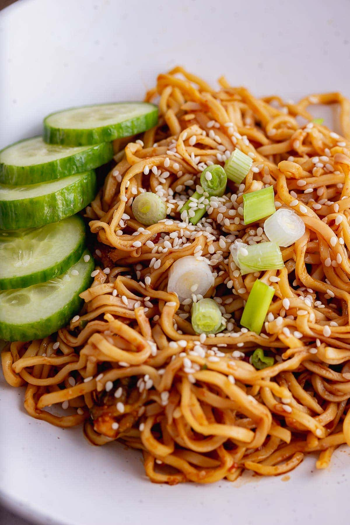 Close up of sesame noodles with spring onion and cucumber