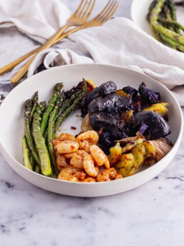 White bowl of harissa prawns with asparagus and potatoes