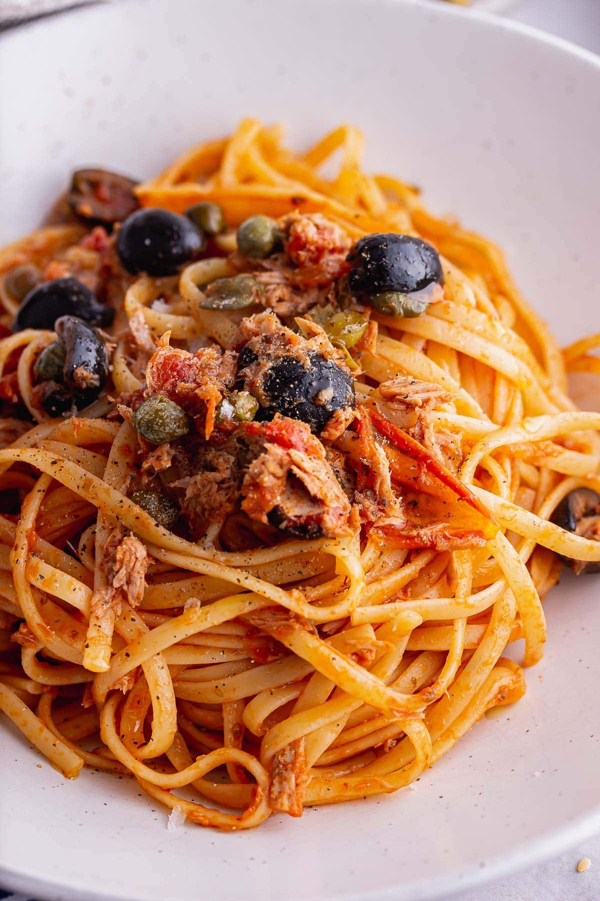 Close up of linguini puttanesca with olives in a white bowl