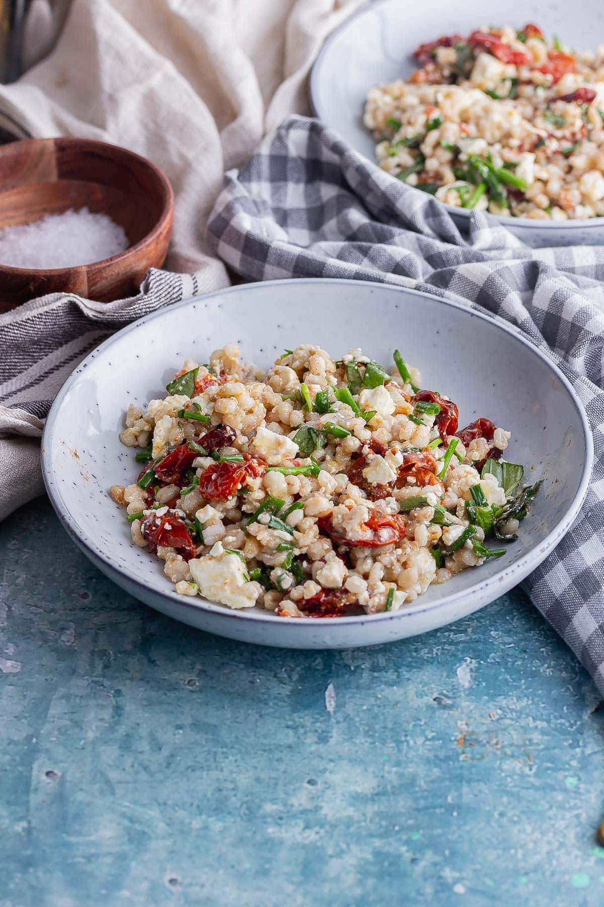 Blue bowl of barley and roast tomato salad on a blue background