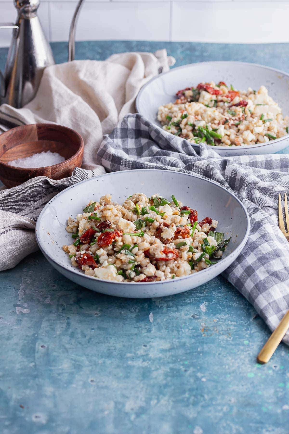 Blue bowl of pearl barley and feta salad with tomatoes with a checked cloth