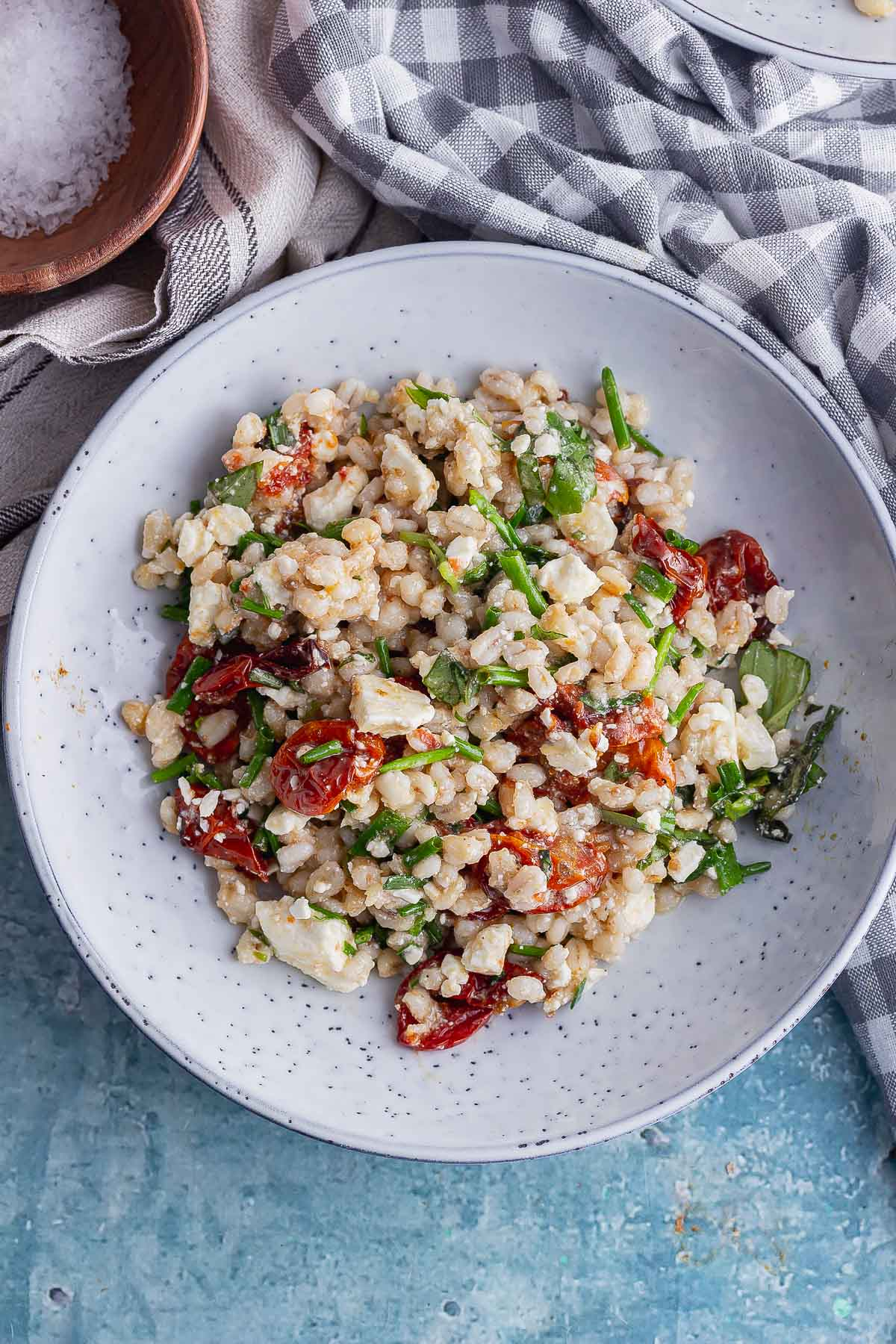 Overhead shot of tomato and barley salad with feta with a checked cloth