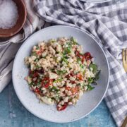 Flat lay shot of a bowl of pearl barley salad with a checked cloth on a blue background
