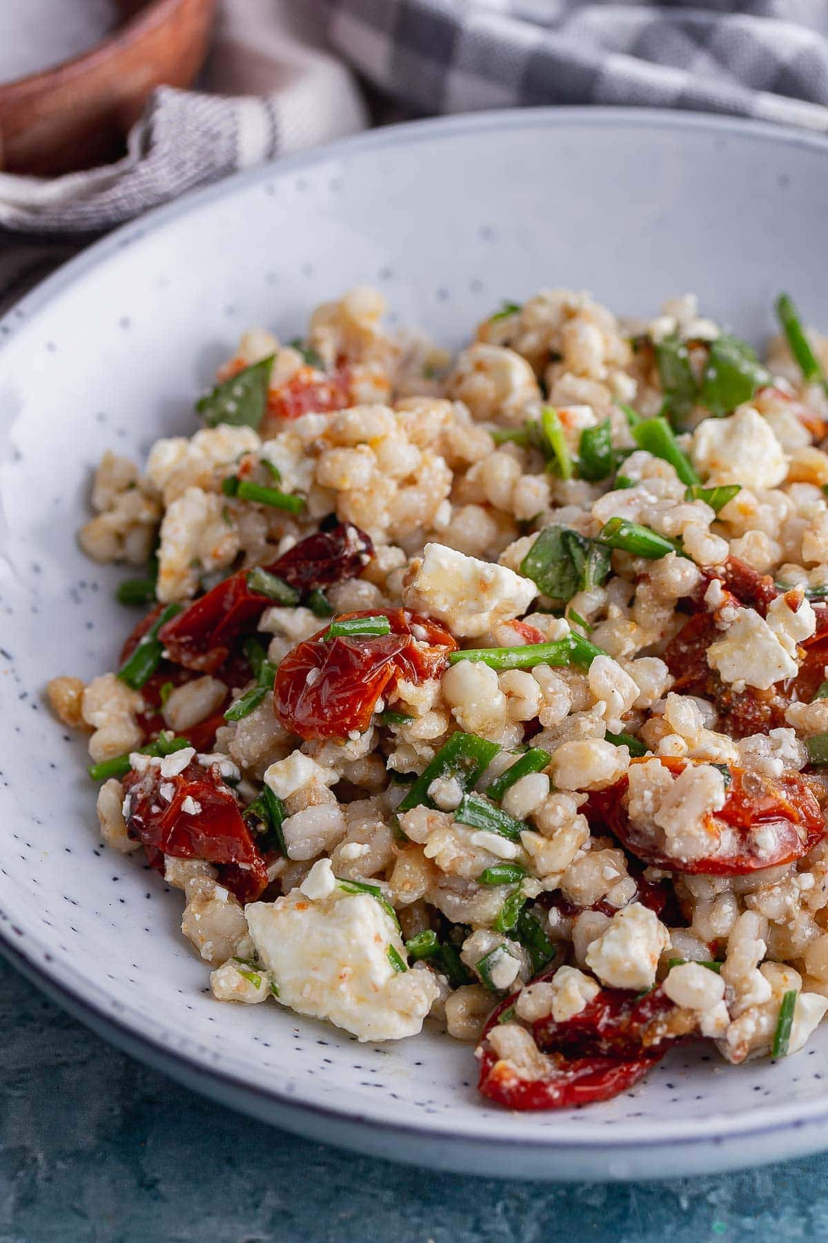 Close up of pearl barley with tomato and herbs in a blue bowl
