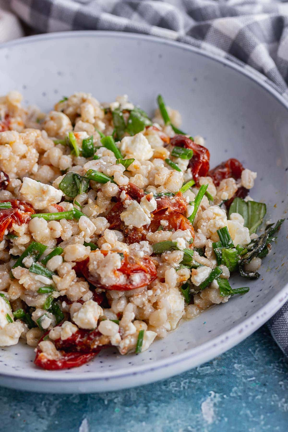 Close up of a pearl barley salad in a blue bowl