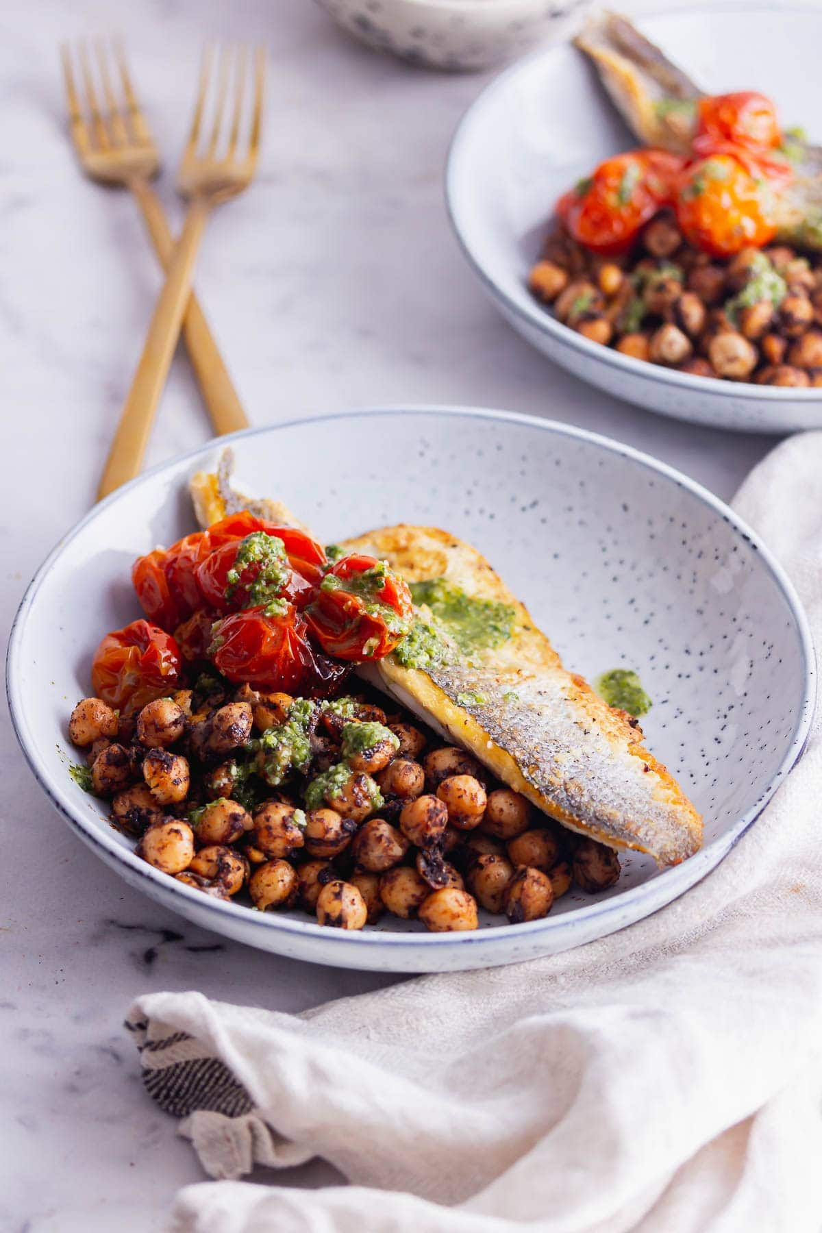 Blue bowl of pan fried sea bass with chickpeas on a marble background