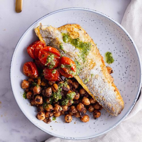 Overhead shot of fried sea bass and chickpeas in a blue bowl