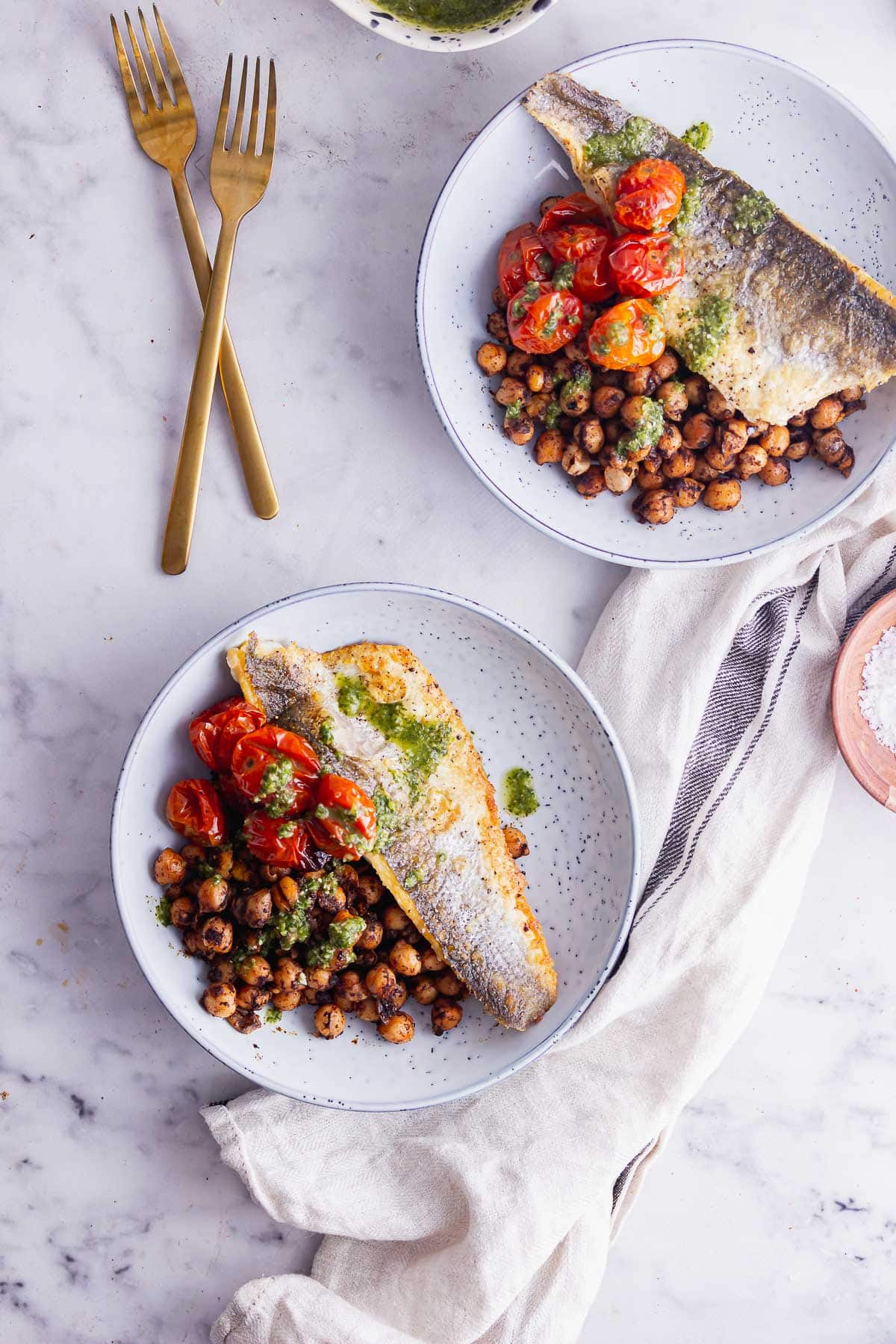 Flat lay shot of blue bowls of pan fried fish over chickpeas on a marble background
