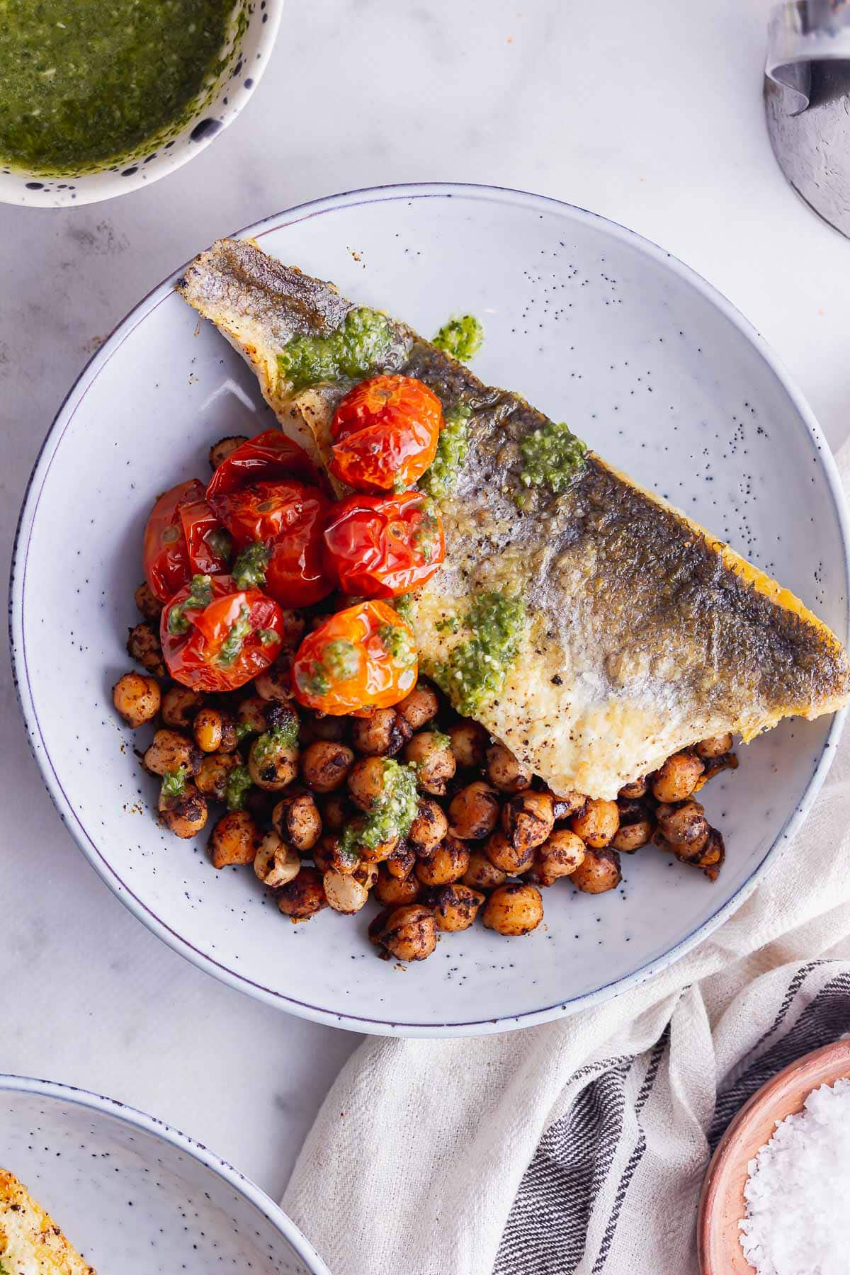 Overhead shot of crispy skin sea bass with tomatoes and chickpeas