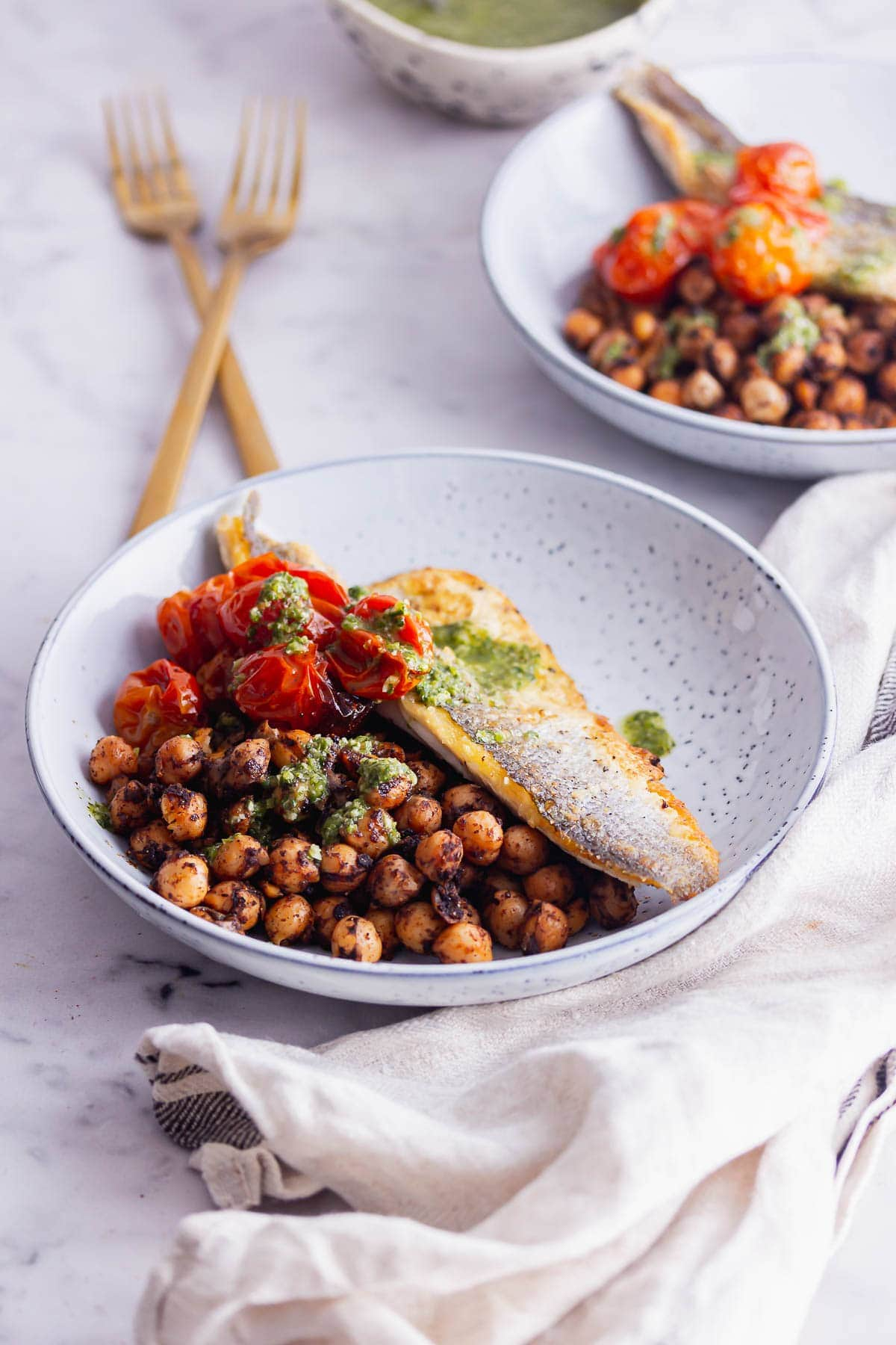 Blue bowl of sea bass and chickpeas with a cloth and gold forks