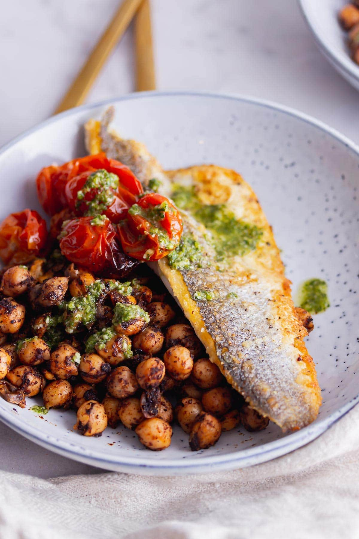 Bowl of crispy fish, chickpeas and tomatoes