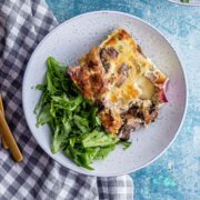 Blue bowl of brunch bake with salad on a checked cloth