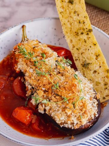 Blue bowl of cheesy roast aubergine with tomato sauce