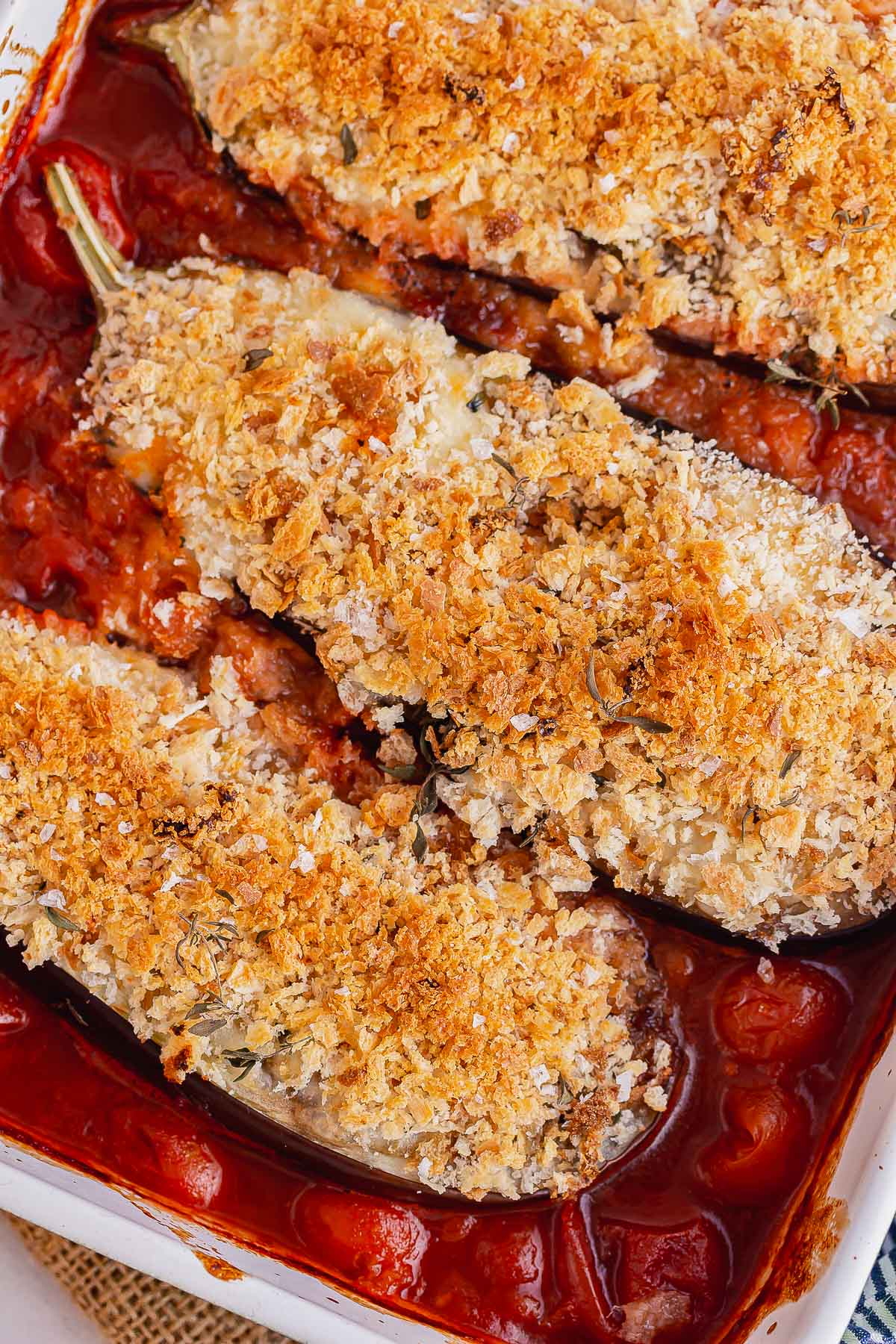 Close up of aubergine topped with breadcrumbs in a tomato sauce