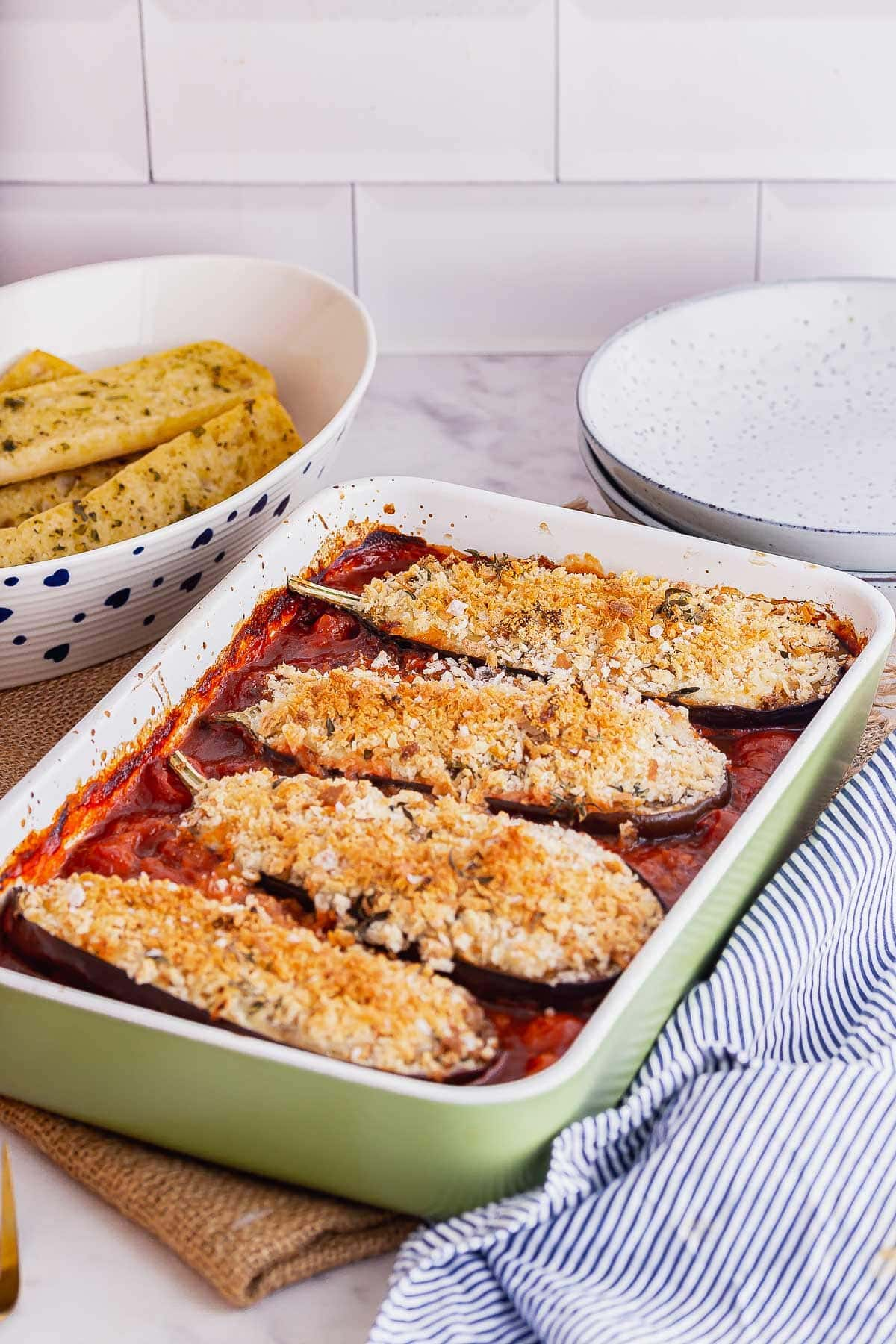Green baking dish of baked aubergine in tomato sauce with a striped cloth