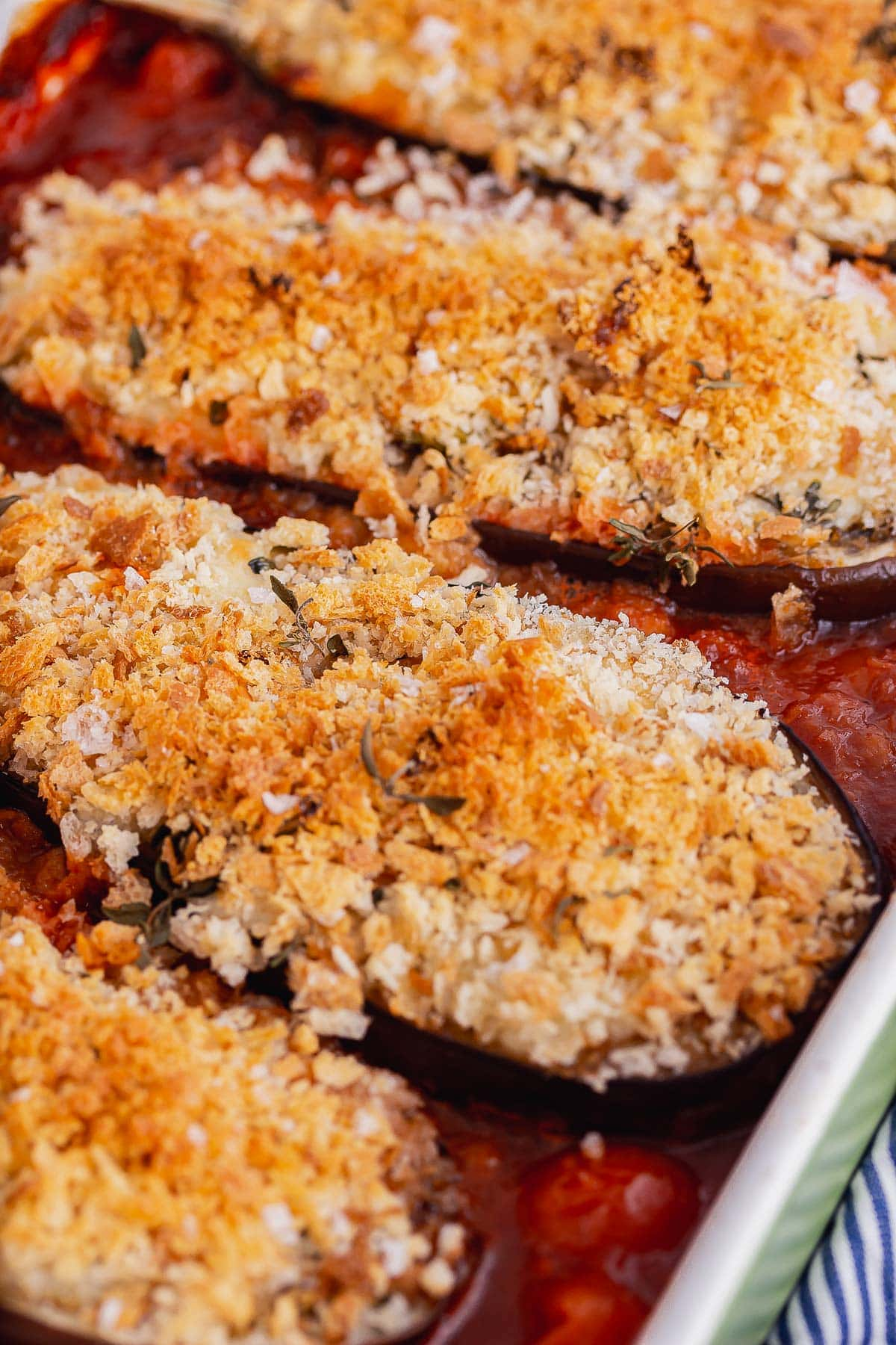 Close up of crunchy topped aubergines in tomato sauce