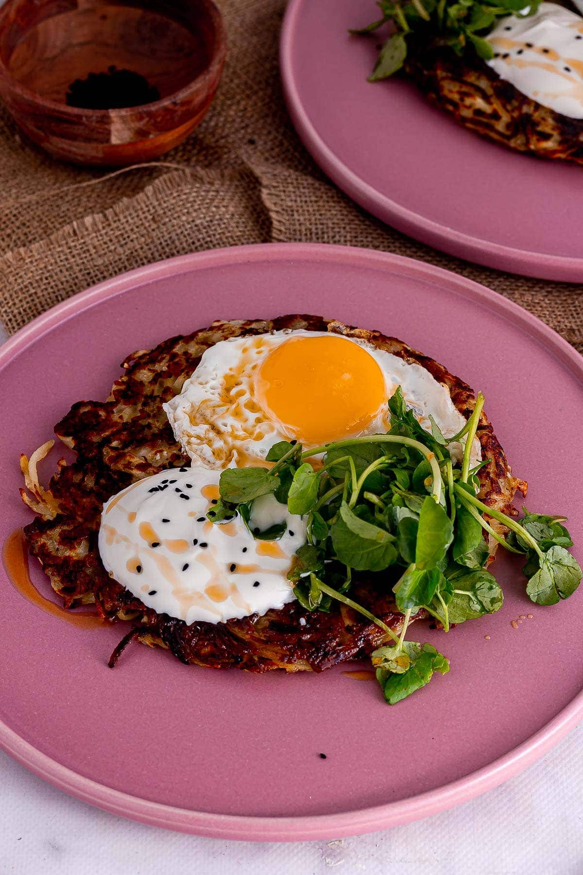 Pink plate of halloumi and potato cake with greens and eggs