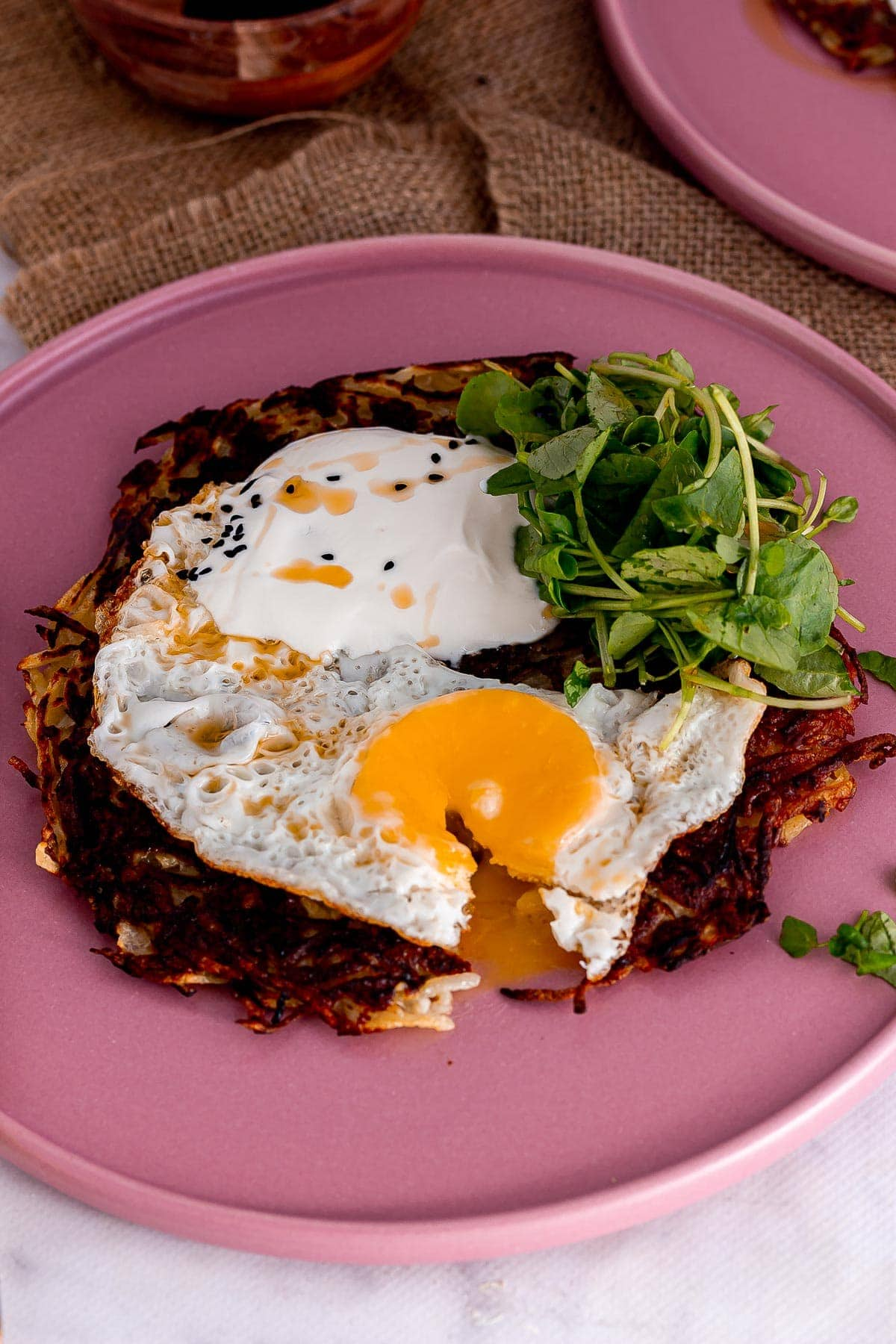 Pink plate of potato cake with a fried egg cut open