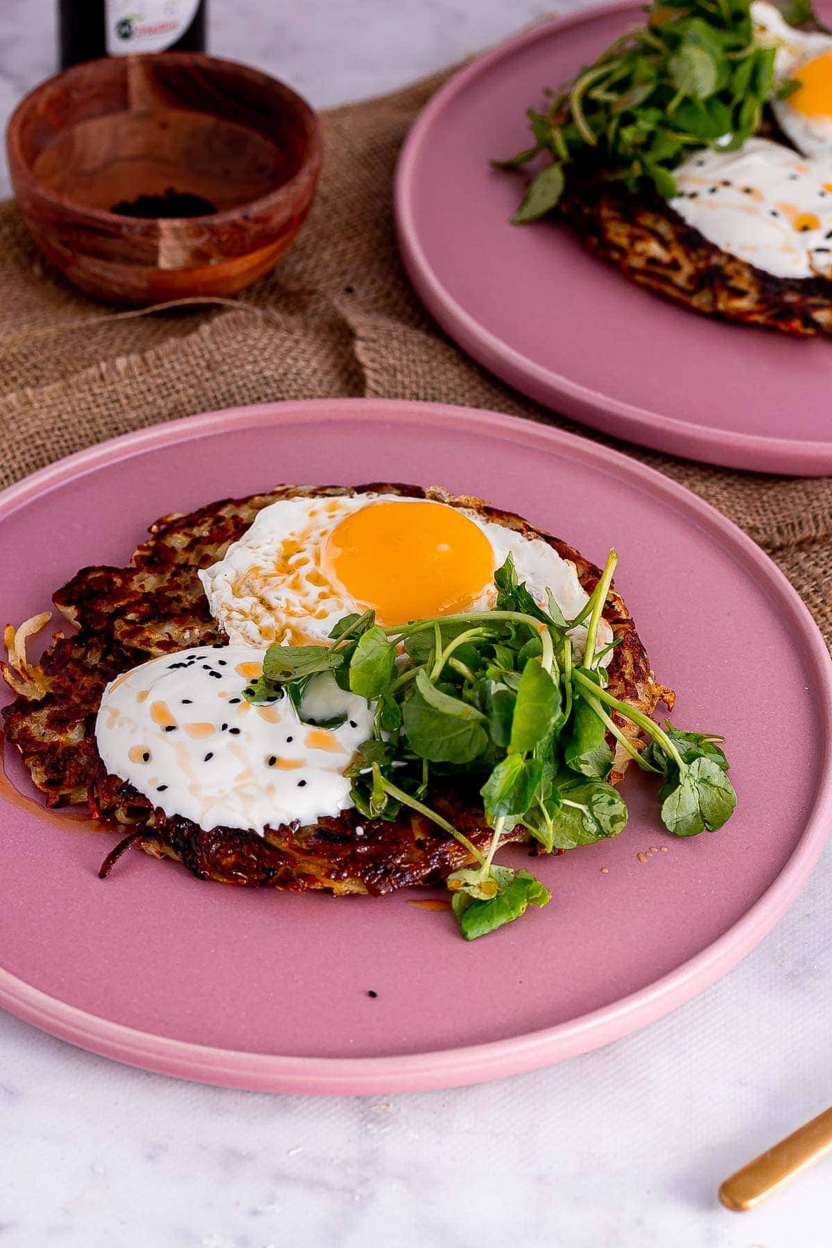 Plate of potato rosti with yoghurt and egg on a marble surface