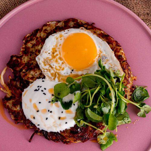 Overhead shot of a fried egg on potato halloumi cake on a pink plate
