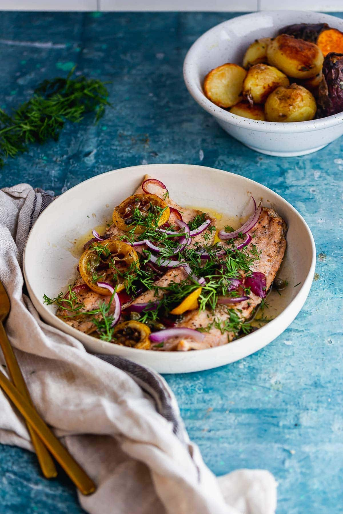 White bowl of baked trout on a blue background