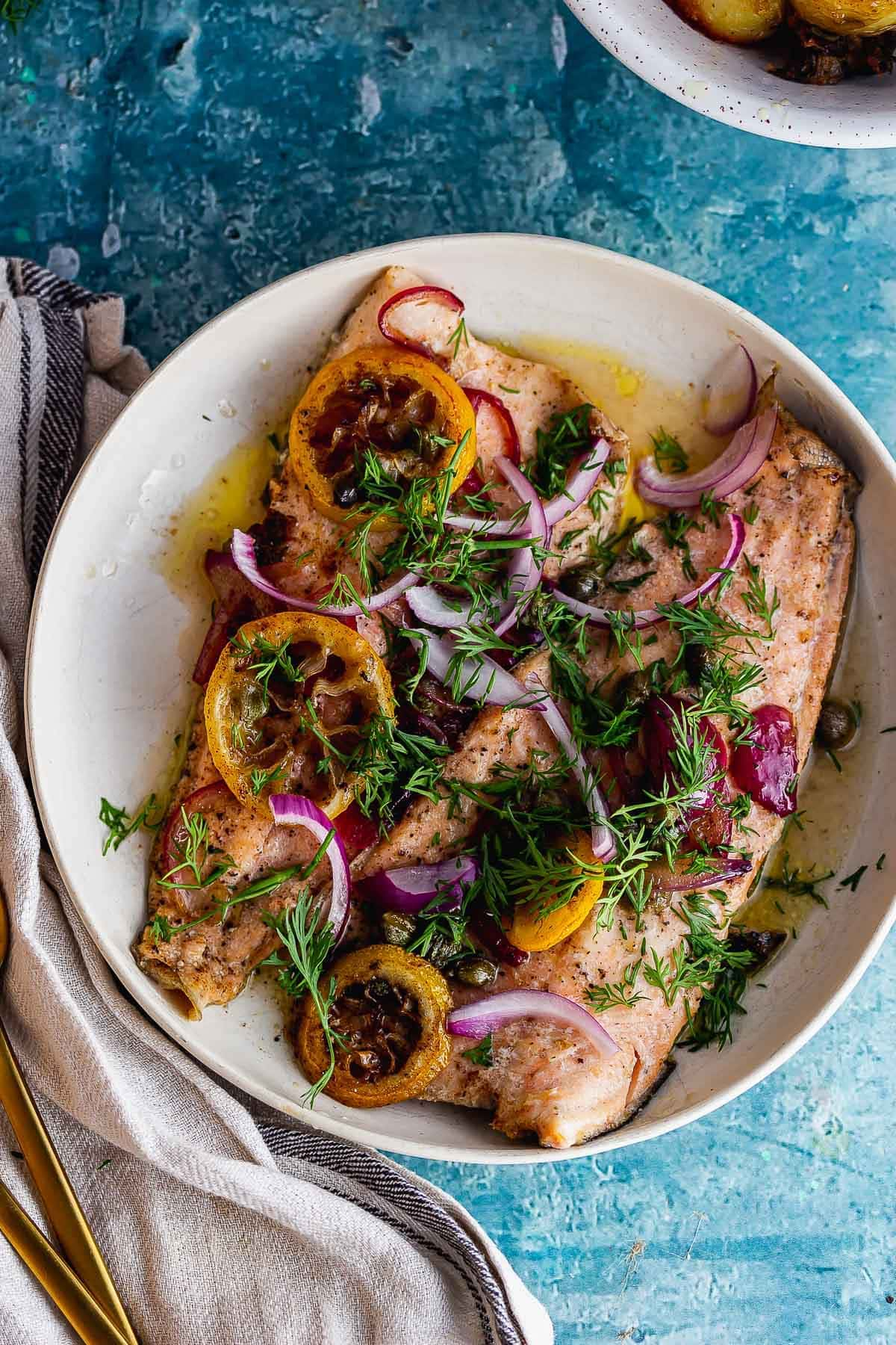Overhead shot of buttery trout with lemon and red onion