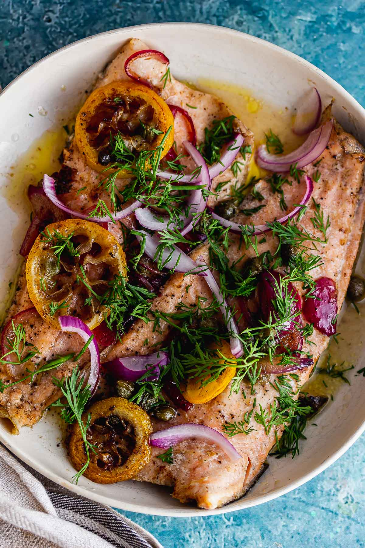 Overhead shot of lemons and red onions on top of trout on a blue background