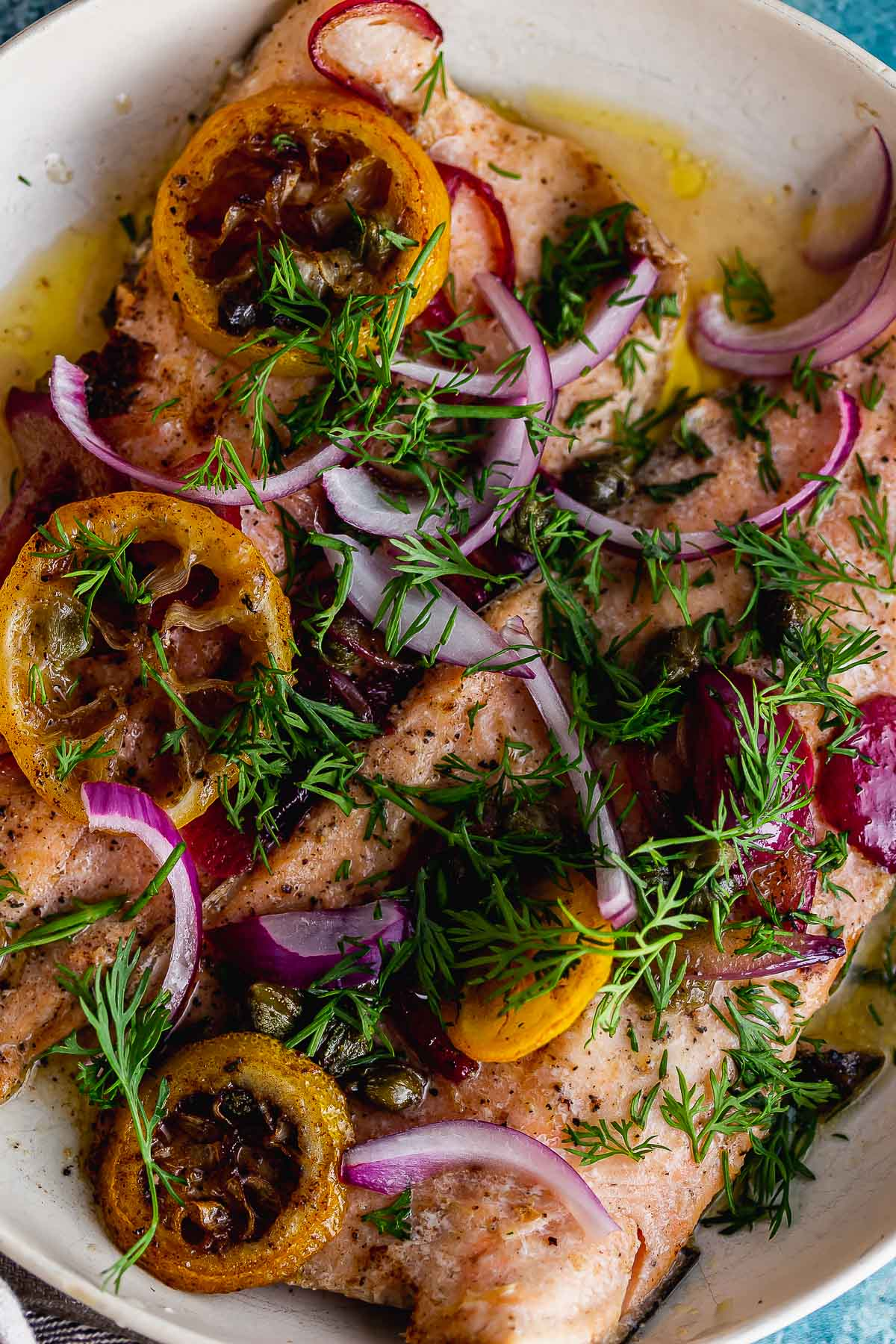 Overhead close up of lemon slices and red onion on top of cooked fish