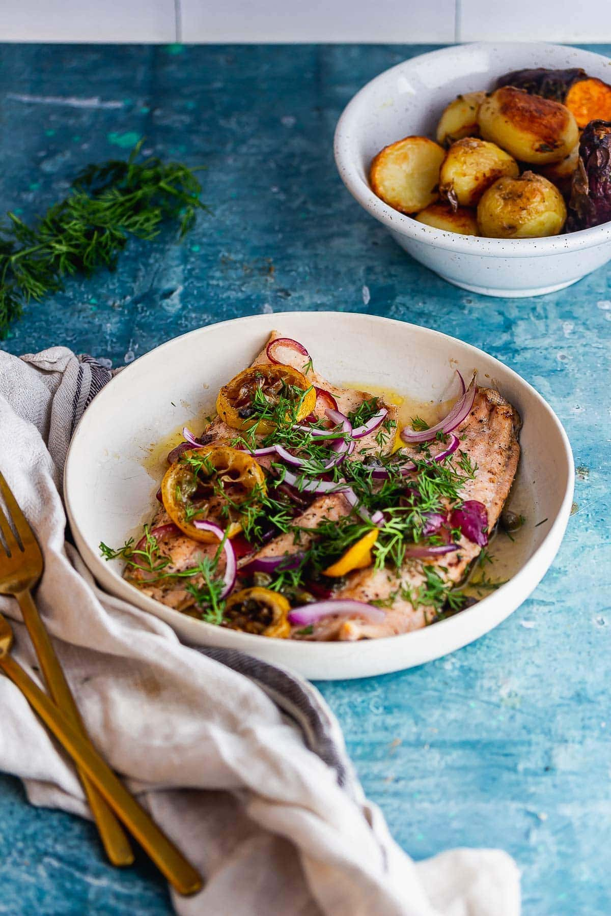 Roasted trout with a cream cloth and gold forks