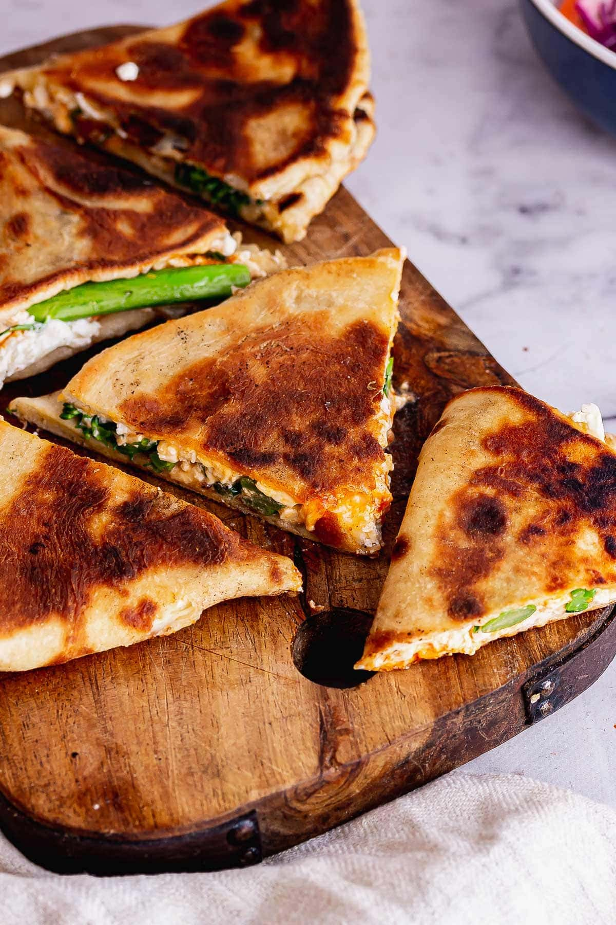 Wooden board with folded flatbreads on a marble background